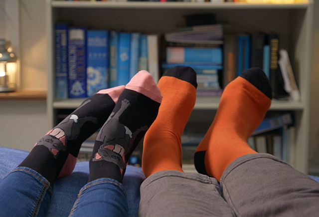 Colourful pair of socks in front of bookcase