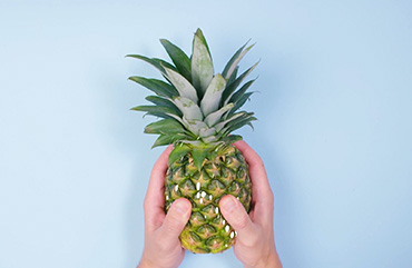 Hands holding a pineapple