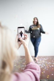 women with confetti having photograph taken