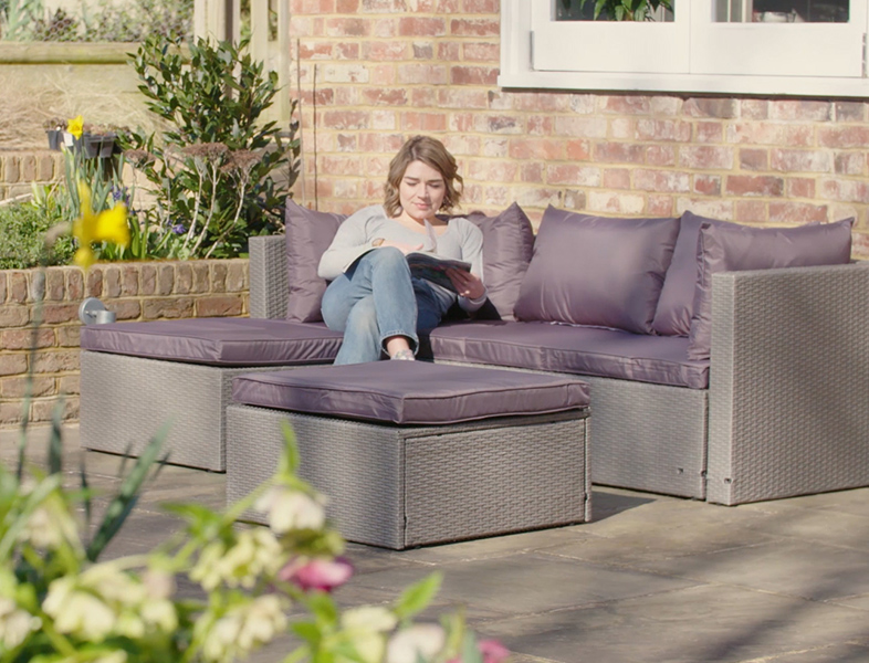Girl sitting on rattan sofa in garden